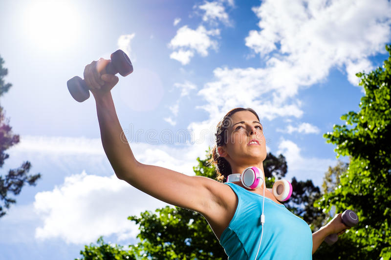 Fitness workout and sport lifestyle woman. Fitness woman working out with dumbbells in city park. Spring or summer exercising workout with weights. Urban sport stock photo