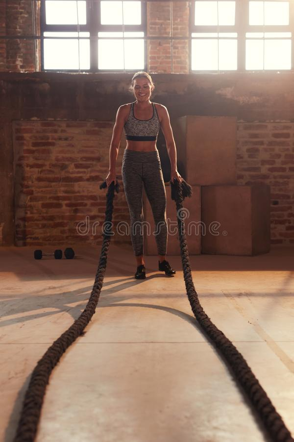 Fitness workout. Sport woman doing battle rope exercise at gym royalty free stock photography
