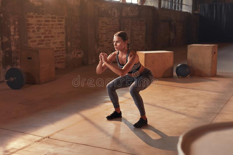 Fitness workout. Sport woman doing squat leg exercise at gym royalty free stock photos
