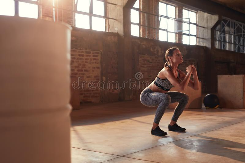 Fitness workout. Sport woman doing squat leg exercise at gym royalty free stock photography