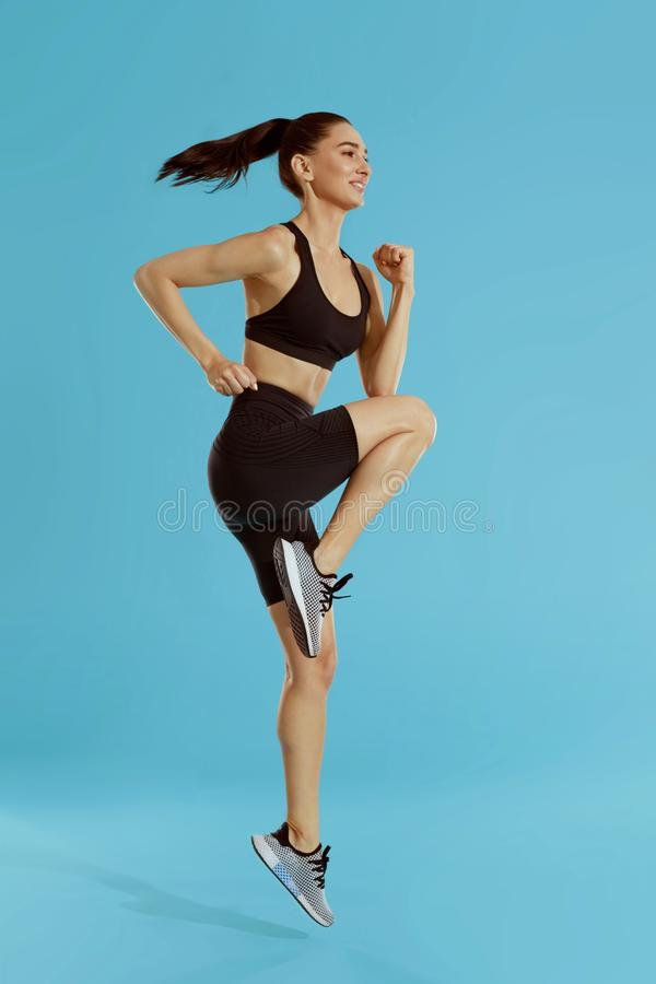 Fitness workout. Woman exercising, jumping on blue background royalty free stock photos