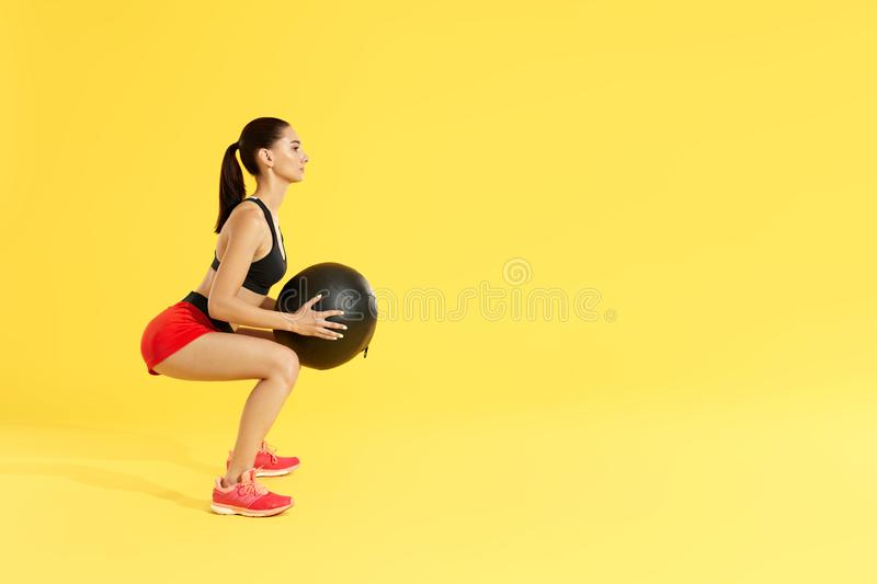Fitness workout. Woman exercising squats with med ball at studio. Fitness workout. Woman in sports wear exercising, doing squats with med ball at studio. Full royalty free stock image