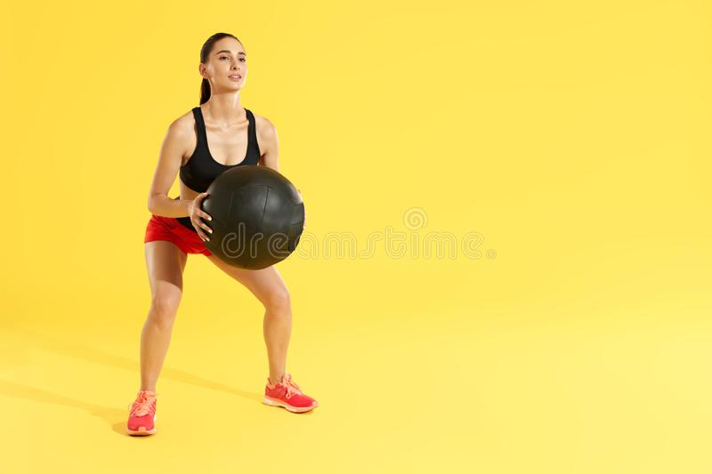 Fitness workout. Woman exercising squats with med ball at studio. Fitness workout. Woman in sports wear exercising, doing squats with med ball at studio. Full royalty free stock images