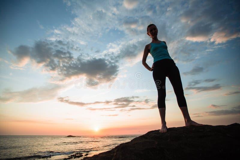 Fitness yoga girl vede al largo del sole sulla costa dell'oceano fotografia stock