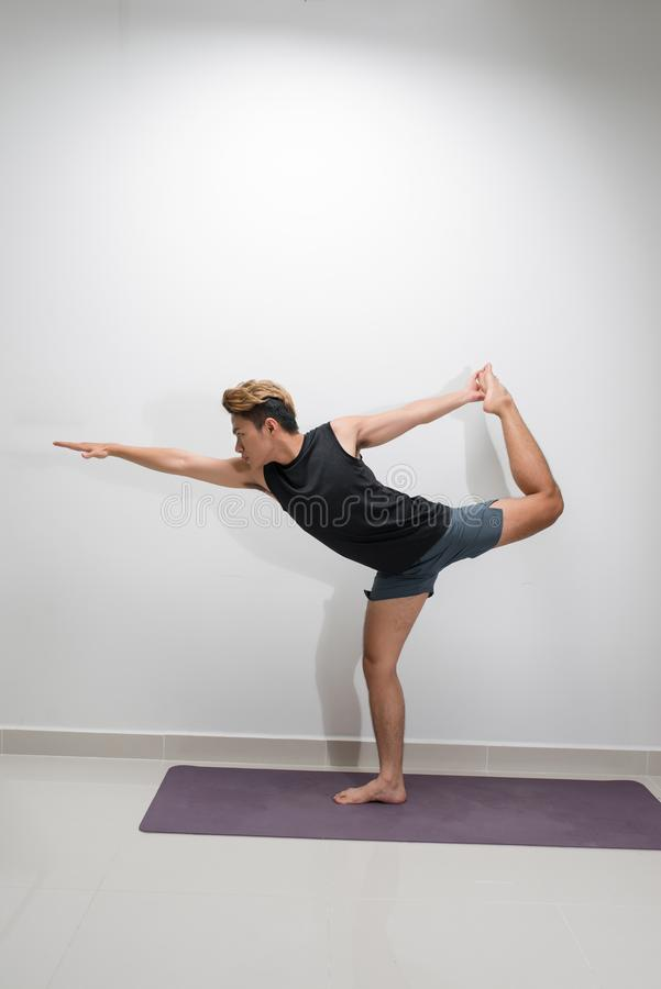 Fitness, yoga and healthy lifestyle concept - doing Warrior pose on mats at studio.  stock photography