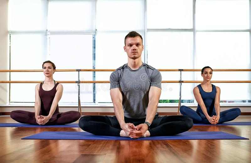 Fitness, yoga and healthy lifestyle concept - group of people doing lotus seal gesture and meditating in seated pose at. Studio royalty free stock photo
