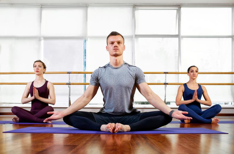 Fitness, yoga and healthy lifestyle concept - group of people doing lotus seal gesture and meditating in seated pose at. Studio royalty free stock photography