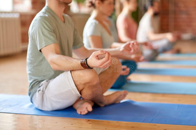 Group of people making yoga exercises at studio stock image