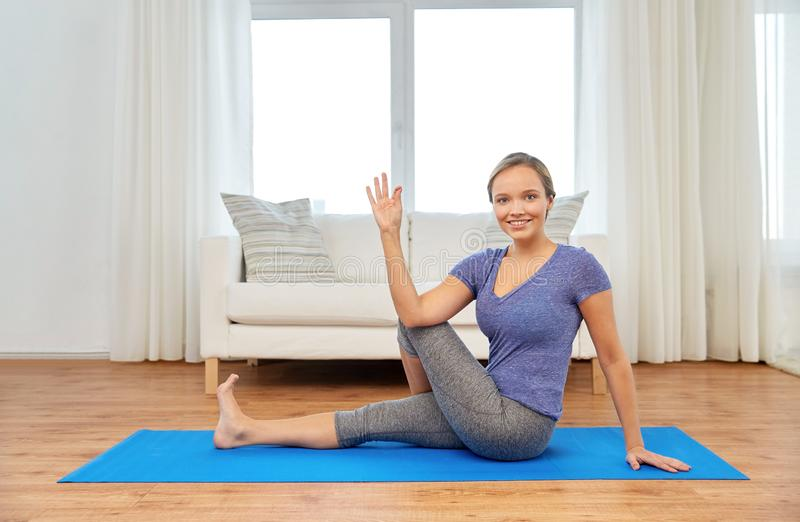 Woman doing half lord of the fishes pose at home stock photography