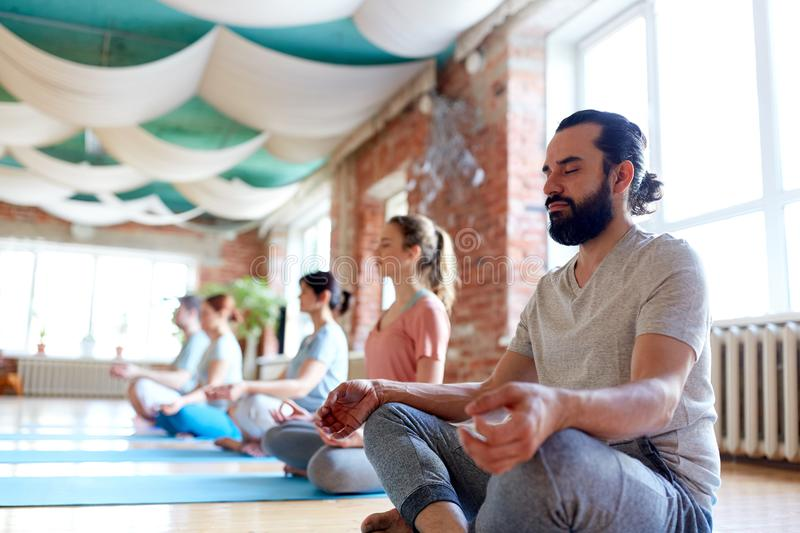 Man with group of people meditating at yoga studio stock photography