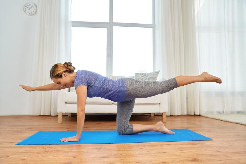 Woman doing yoga cat pose at home stock photography