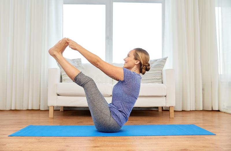 Woman doing yoga double toe hold pose at home royalty free stock images