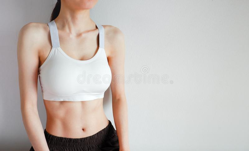 Fitness and Yoga Healthy Lifestyle Concept. Young Woman Wearing White Sport Bra and Pants with Muscular Body and Strong Six Pack royalty free stock photo