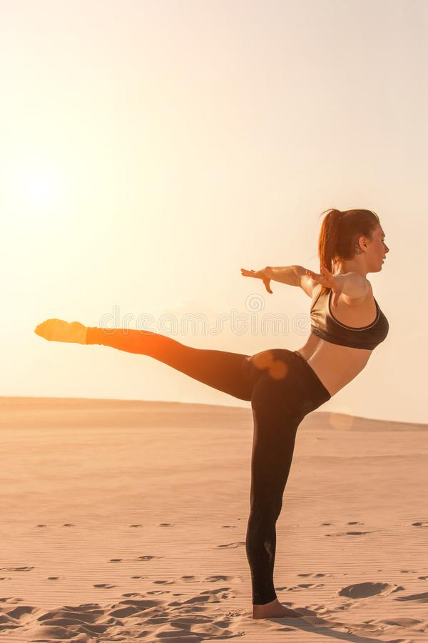 Fitness yoga woman stretching on sand. Fit female athlete doing yoga pose. Fitness yoga woman stretching on sand. Fit female athlete doing yoga pose before stock photos