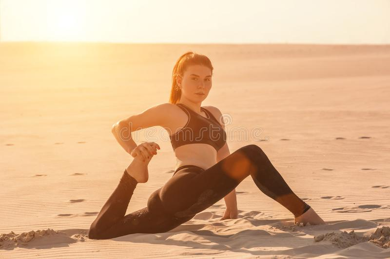 Fitness yoga woman stretching on sand. Fit female athlete doing yoga pose. Fitness yoga woman stretching on sand. Fit female athlete doing yoga pose before stock photography