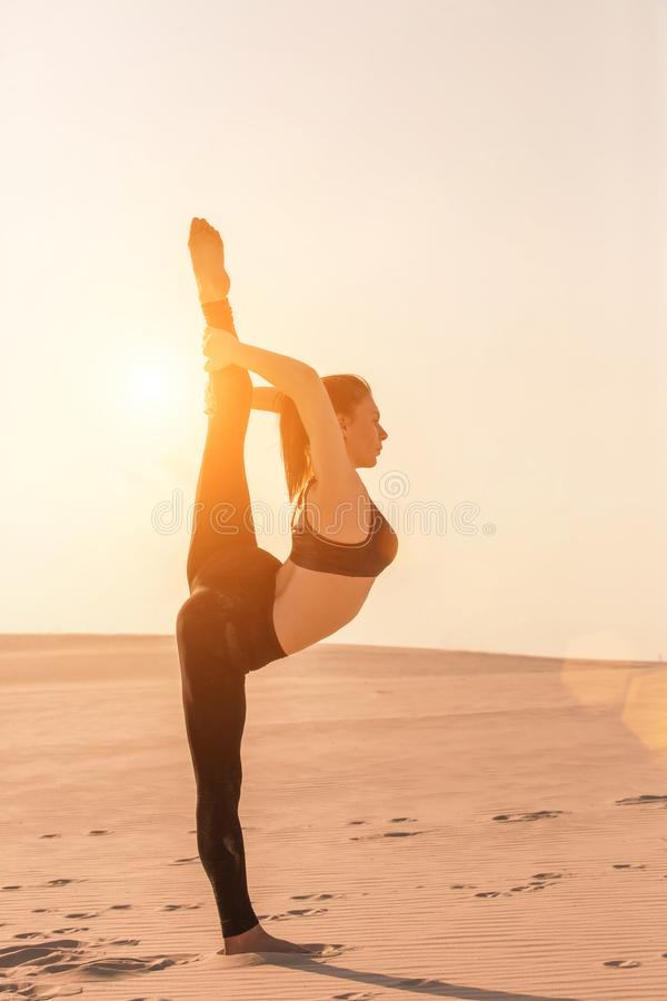 Fitness yoga woman stretching on sand. Fit female athlete doing yoga pose. Fitness yoga woman stretching on sand. Fit female athlete doing yoga pose before stock images