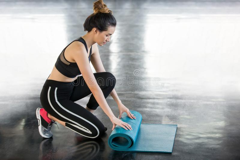 fitness young asian woman rolling blue yoga mat after workout in gym royalty free stock images