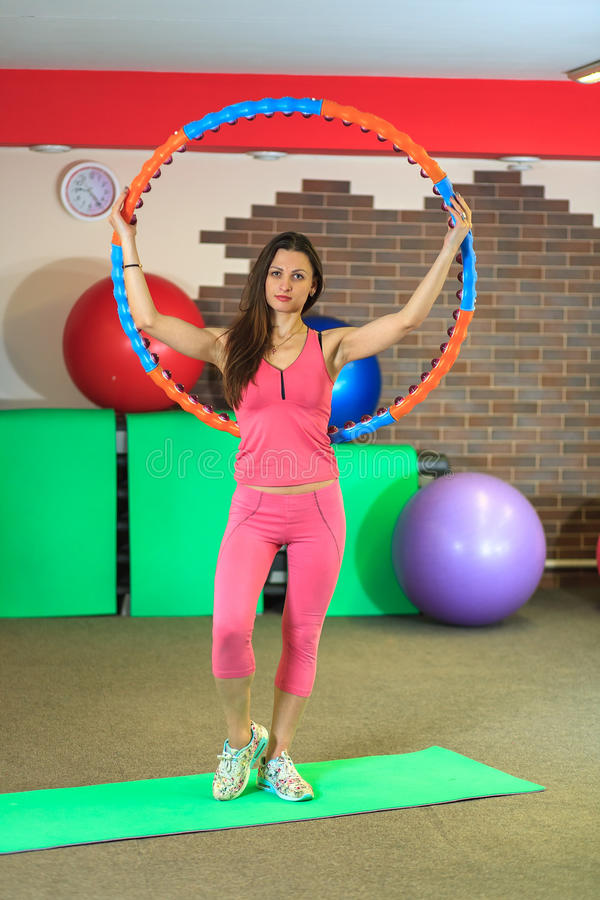 Fitness. Young beautiful white girl in a pink sports suit does physical exercises with a hoop at the fitness center. Young beautiful white girl in a pink sports royalty free stock image