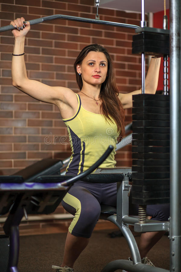 Fitness. Young beautiful white girl in a yellow and gray sports suit is doing exercises on training apparatus. Young beautiful white girl in a yellow and gray royalty free stock photography