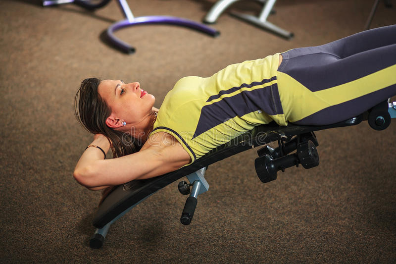 Fitness. Young beautiful white girl in a yellow and gray sports suit is doing exercises on training apparatus in the fitness club. Young beautiful white girl in stock photos