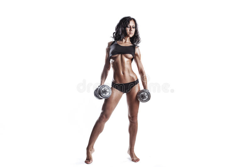 Fitness young brunette woman posing with dumbbells isolated. In studio over white isolated stock photos