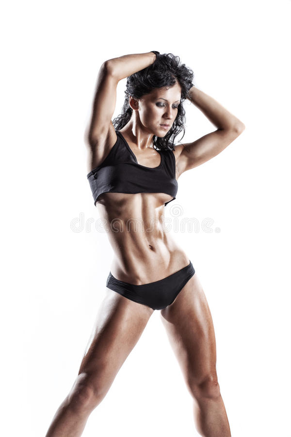 Fitness young brunette woman posing over white isolated. Fitness young brunette woman posing in black wear isolated in studio over white isolated stock image