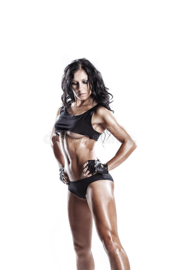 Fitness young brunette woman posing over white isolated. Fitness young brunette woman posing in black wear isolated in studio over white isolated royalty free stock photography