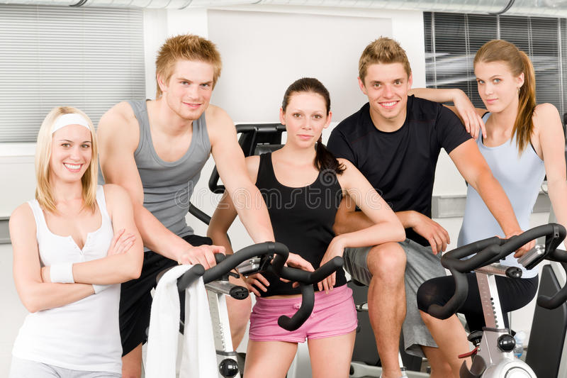 Fitness young group people at gym bicycle royalty free stock photo