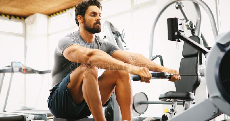 Fitness young man using rowing machine royalty free stock photos