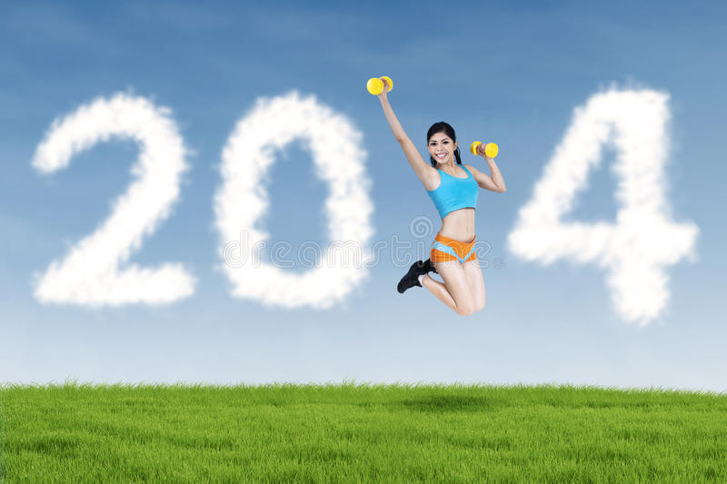 Fitness young woman jumping with new year 2014 royalty free stock image