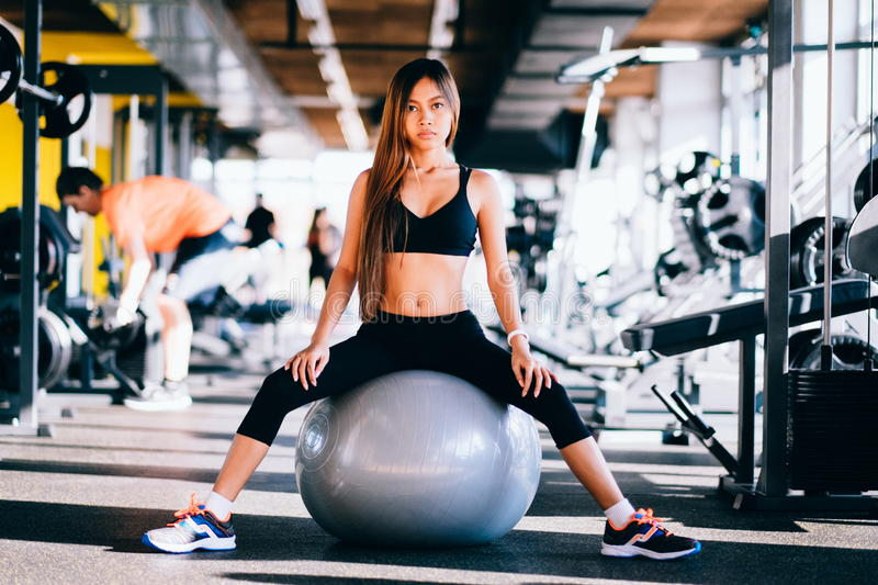 Fitness young woman with long hair in gym, sitting on Pilates ball.  stock photography
