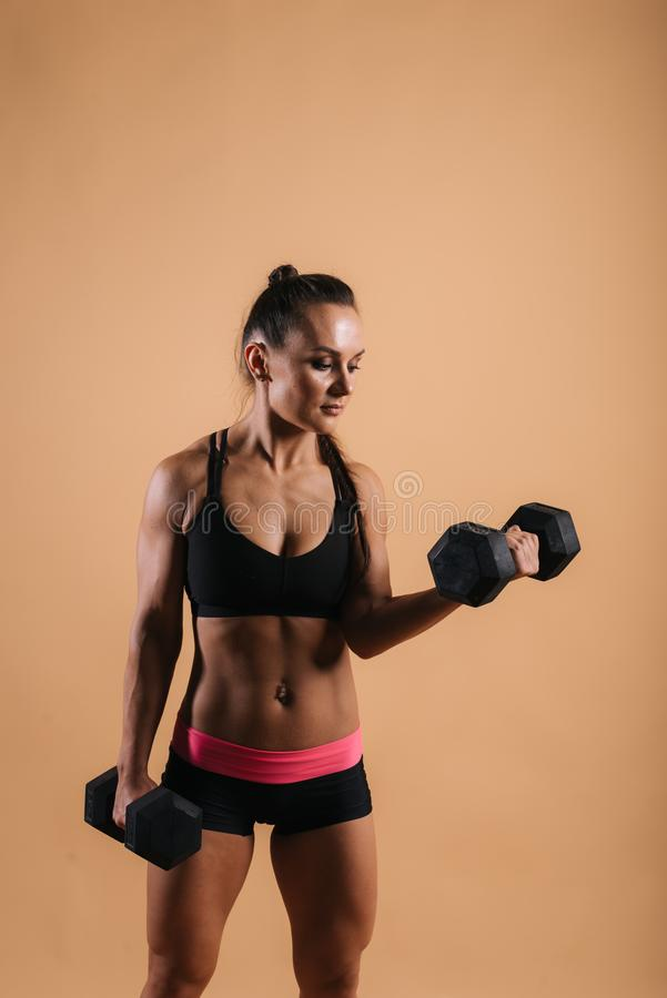 Fitness young woman with perfect muscular body is posing with two dumbbells stock images