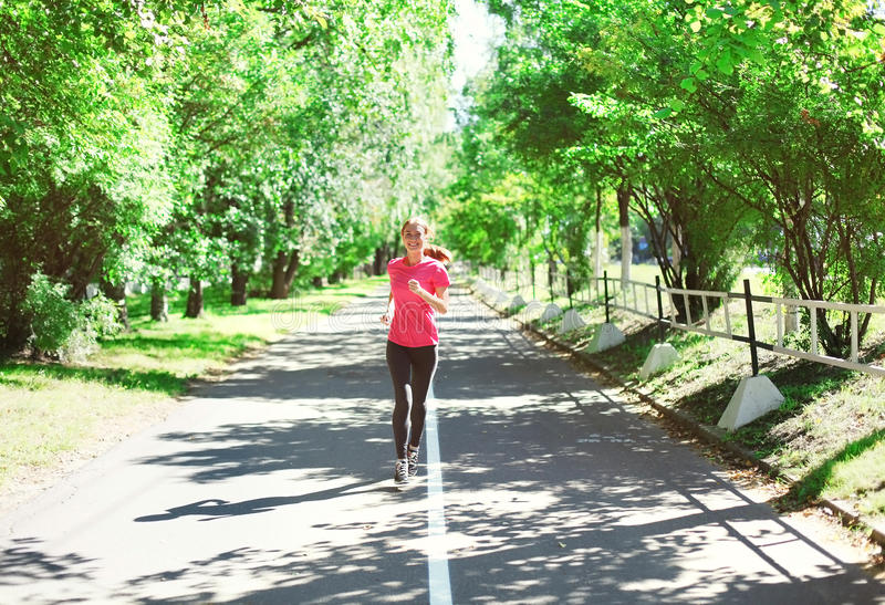 Fitness young woman running in summer park, female runner workout - sport and healthy lifestyle royalty free stock image