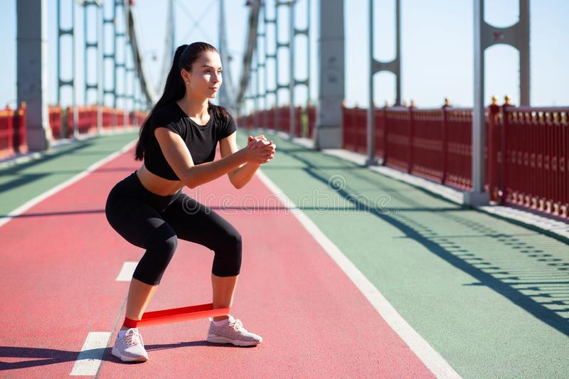 Fitness brunette girl in sport apparel crouching using resistance band while workout. Empty space. Fitness young woman in sport apparel crouching using stock image