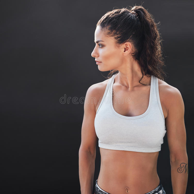 Fitness young woman in sportswear. Standing on black background. Slim and healthy female model in studio stock photography