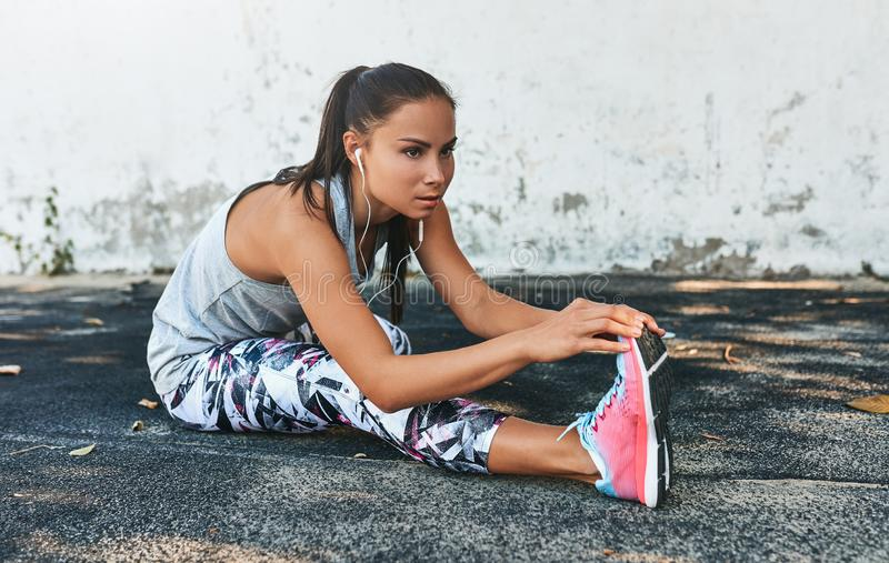 Fitness young woman streching and listening the music on earphones before outdoors against concrete wall. Athletic female strech. After workout outside. Sport stock image