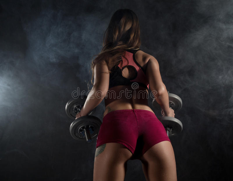 Fitness young woman in training with dumbbells, sporty muscular female brunette in smoke. Girl wearing sports clothes working out with dumbbell over white stock photography