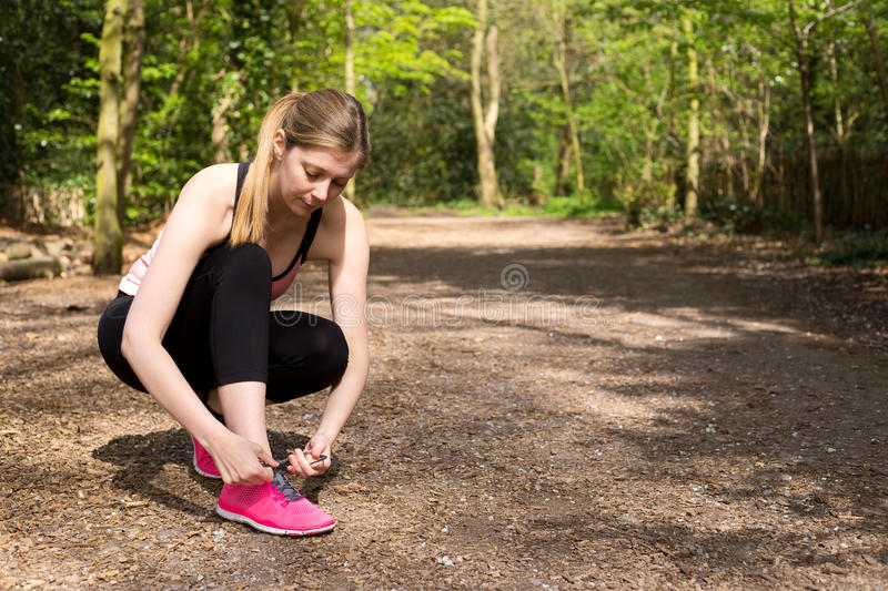 Fitness. A young woman tying her laces while out running royalty free stock photo