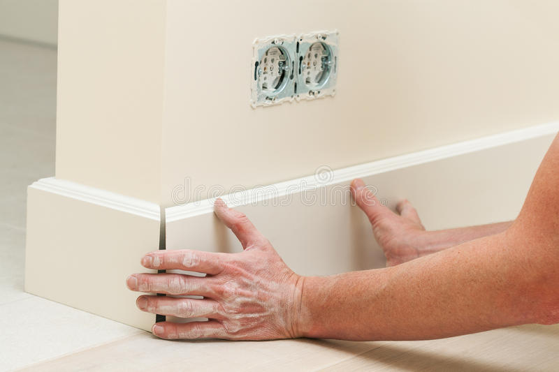 Fitting the baseboard. Hands fitting the baseboard to a bright wall royalty free stock images