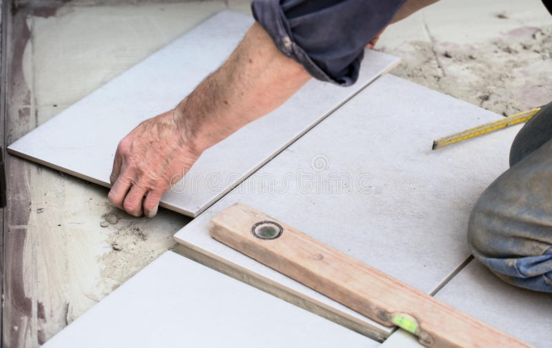 Fitting a floor tile stock photo