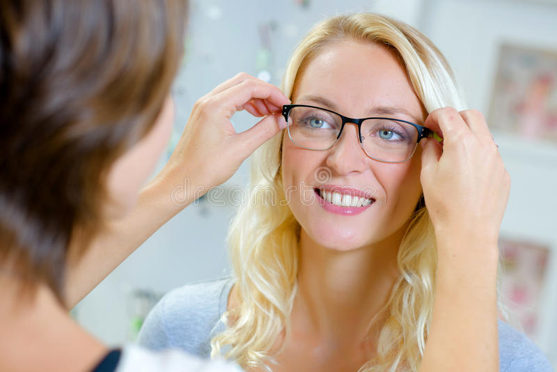 Fitting glasses onto lady royalty free stock photos