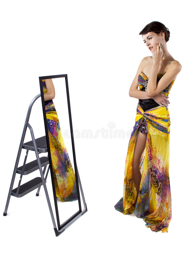 Fitting Room Mirror. Young female wearing clothes in a fitting room with a mirror stock photo