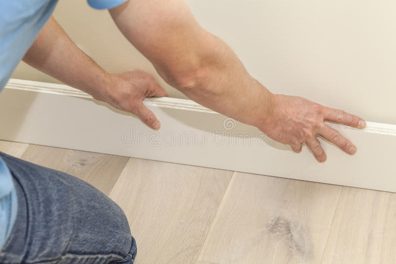 Fitting the skirting board. Mans hands fitting new wooden skirting board royalty free stock photo