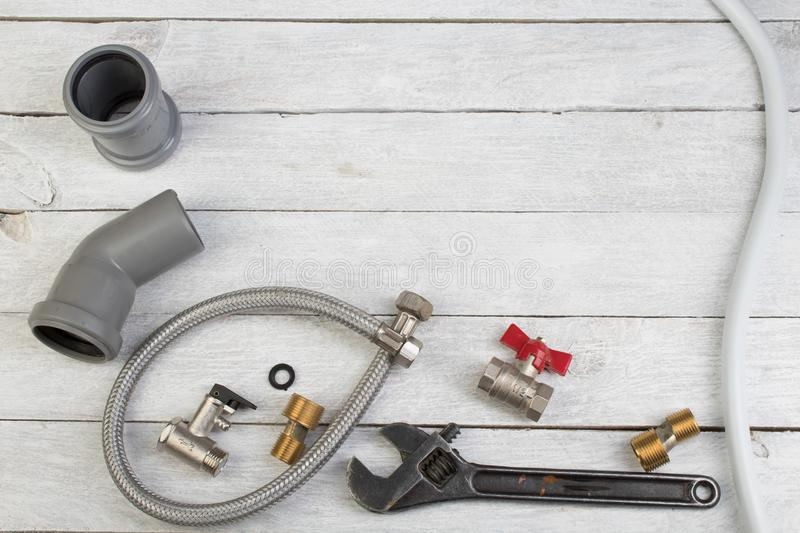 Fittings, pipe, valves, plastic pipe for water, water hose, adjustable wrench on the wooden background. Top view. Copy royalty free stock images
