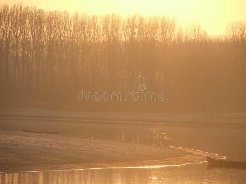 Fiume alla luce di tramonto, con la foresta e le barche fotografia stock libera da diritti