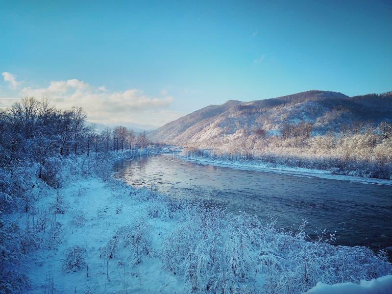 Fiume con ghiaccio su un fondo delle montagne fotografia stock