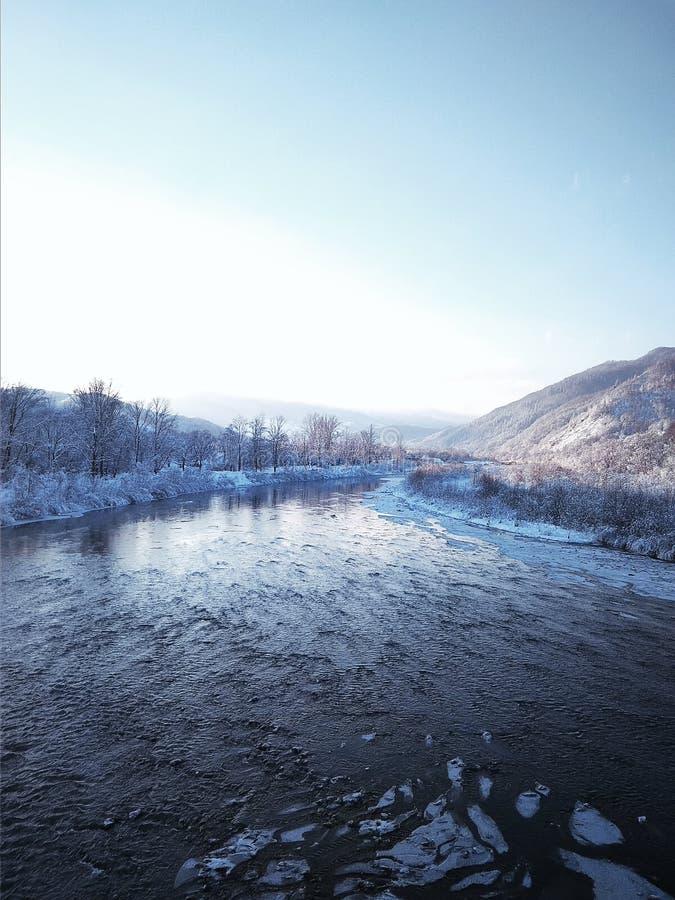 Fiume con ghiaccio su un fondo delle montagne fotografie stock