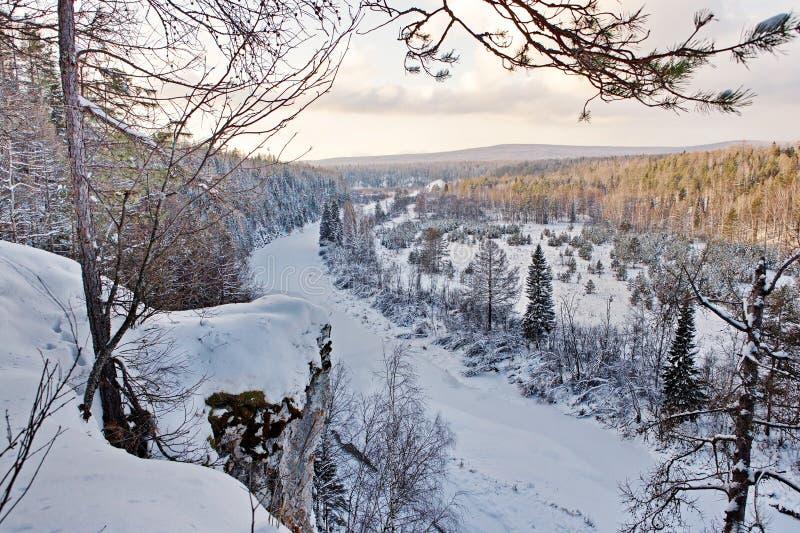 Fiume congelato sui precedenti delle montagne e del taiga nevosi Natura selvaggia L'Estremo Oriente, isola di Sakhalin fotografie stock libere da diritti