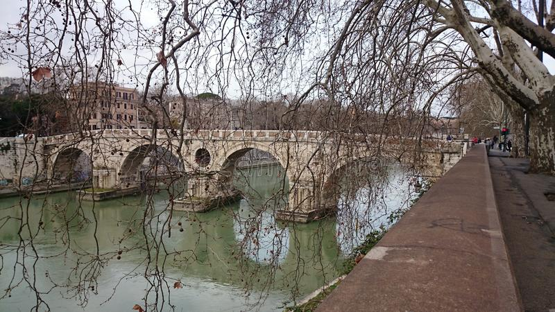 Fiume del Tevere con un ponte antico a Roma, Italia immagini stock libere da diritti