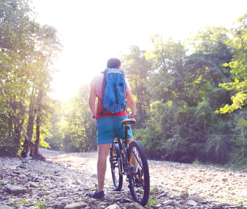 Fiume della montagna dell'incrocio dell'uomo dell'atleta con la bicicletta fotografia stock